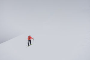 A man climbing a steep snowy hillside on skis