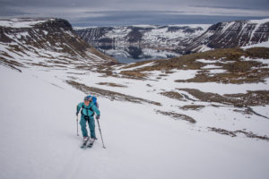 A woman climbing a snowy hillside on skis