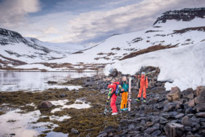A group of women hold their skis on the rocky shoreline of a lake