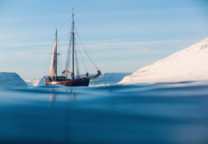 A boat sailing next to an icy shore line
