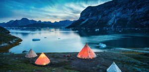 A group of teepee style tents camped by a Greenland Fjord