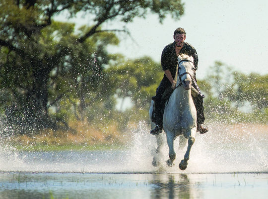 Duncan Over crossing a river riding a horse