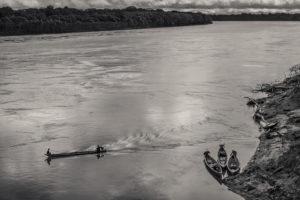 A motorised canoe travels down jungle river