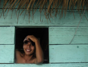 A man stares out of the window of a jungle house